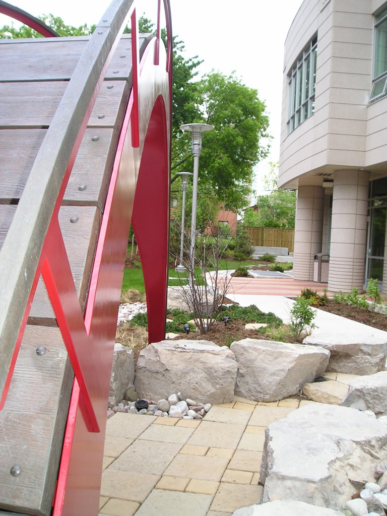 The Bridge Details <br>The 'bridge' architectural details and garden.  Roughhewn lumber has been used in concert with brightly painted metal frames to create the sculpture.  The smooth lines of the bridge are contrasted with the organic forms of the natural materials.