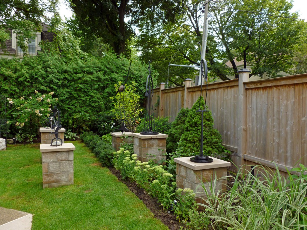 A series of stone plinths are embedded in the garden for the owner's display of sculptures