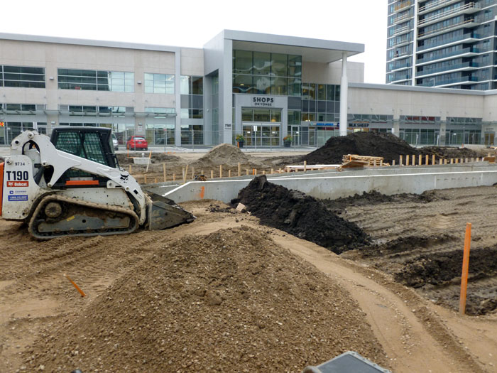 Equipment placing fill under future hard (paved) and soft (planted) areas.
