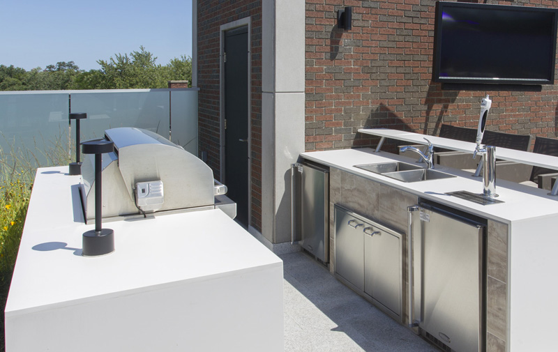 The outdoor kitchen is complete with BBQ, fridge, sink, tap, and outdoor beverage dispenser.